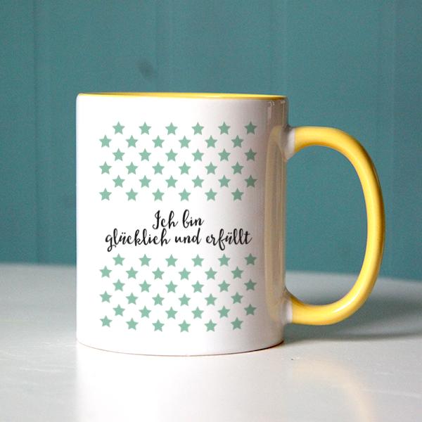 """""""Ich bin glücklich und erfüllt"""" als positiver Glaubenssatz mit grünen Sternchen auf einer gelben Tasse"""